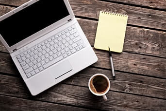 Laptop (notebook) with cup of coffee and notepad with pen on old wooden table.